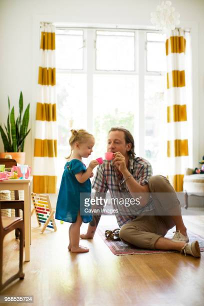 father playing tea party with daughter at home - tea party stock pictures, royalty-free photos & images