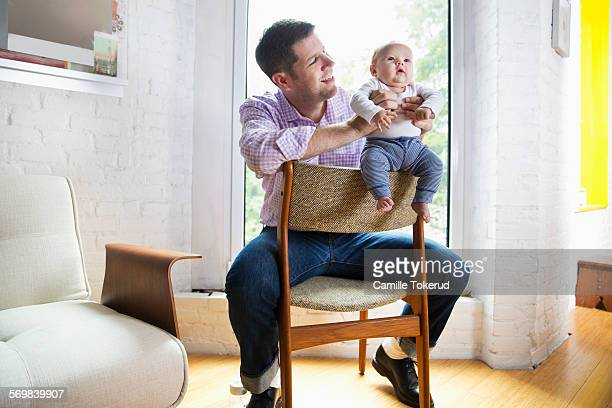 Father playing with baby in livingroom