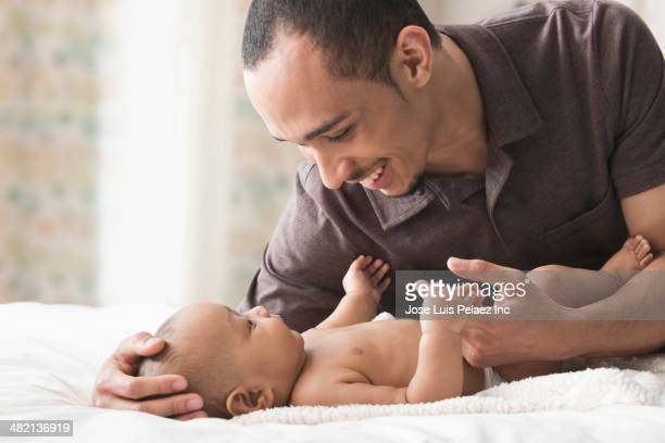 Father playing with baby on bed