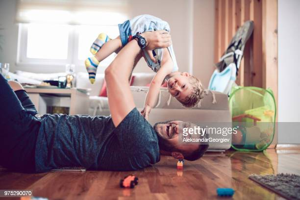 father playing with baby son in living room - pai imagens e fotografias de stock