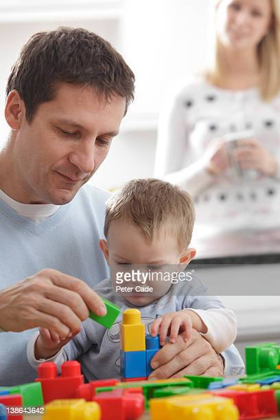 father playing with baby while mother watches