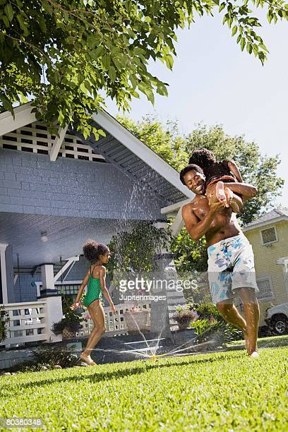 Father playing with children in front lawn sprinkler