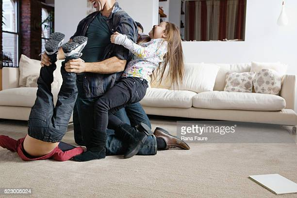 Father playing with children in living room