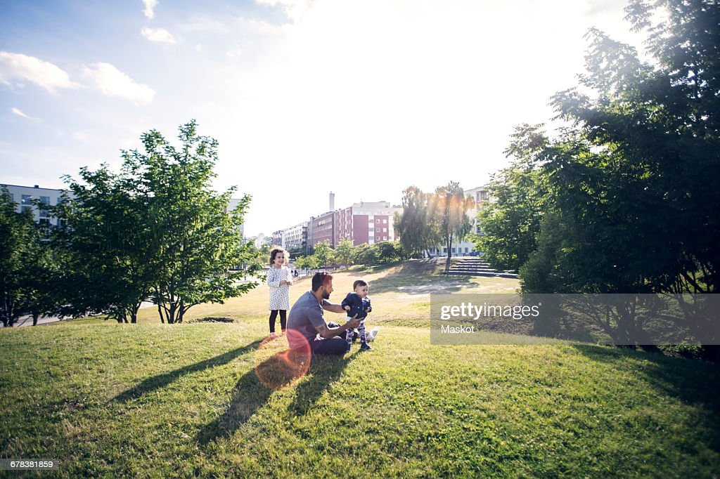 Father playing with children on grassy field at park against sky : Stock Photo