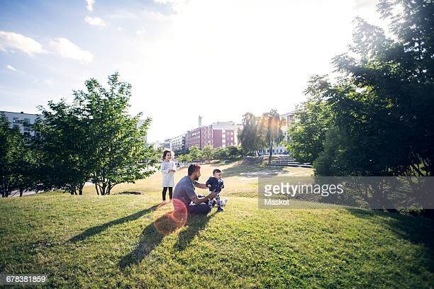 father playing with children on grassy field at park against sky - stadtviertel stock-fotos und bilder