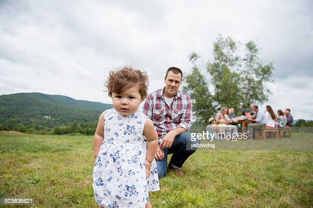 Father playing with daughter at family gathering, outdoors