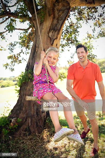 Father playing with daughter at rope swing