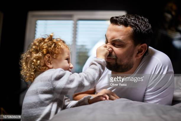 Father playing with daughter in bed