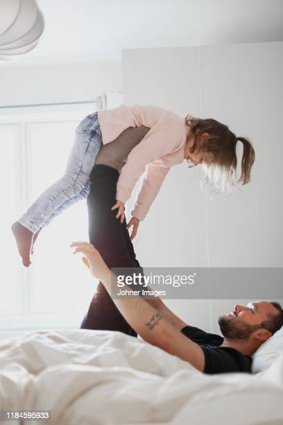 father playing with daughter in bed - norway stock pictures, royalty-free photos & images