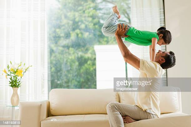 father playing with daughter (6-7) in living room - indian subcontinent ethnicity stock pictures, royalty-free photos & images