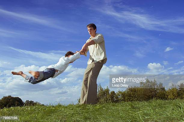 Germany, Father playing with daughter (6-7) in meadow