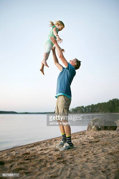 Father playing with daughter on beach