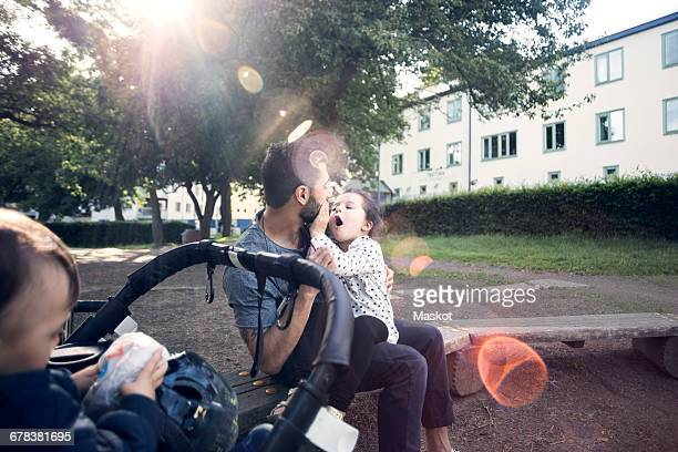 Father playing with daughter while sitting on bench by baby stroller at park
