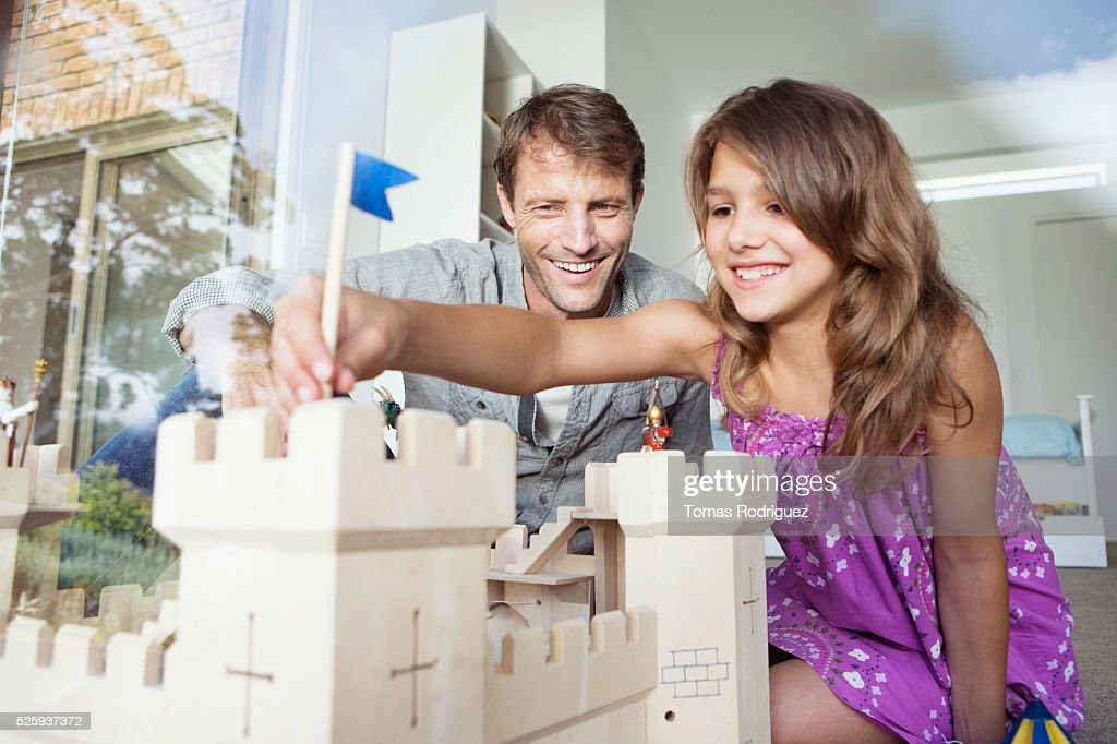 Father playing with daughter (8-9) with model of castle : Stock Photo