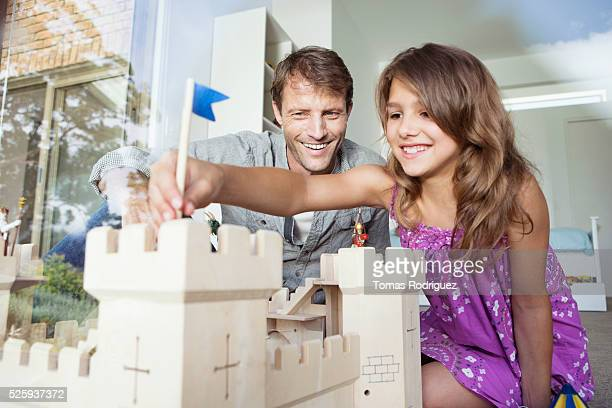 Father playing with daughter (8-9) with model of castle