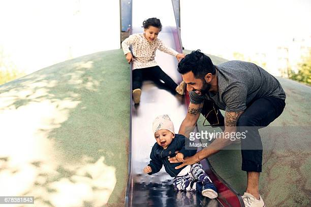 Father playing with daughters on slide at park