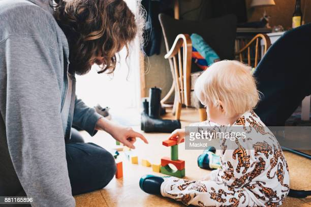 Father playing with girl while sitting at home