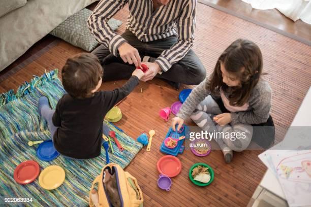 Padre jugando con sus hijos en casa