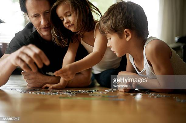 Father playing with his children, lying on floor