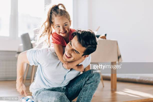 father playing with his little girl at home - fathers day stock pictures, royalty-free photos & images