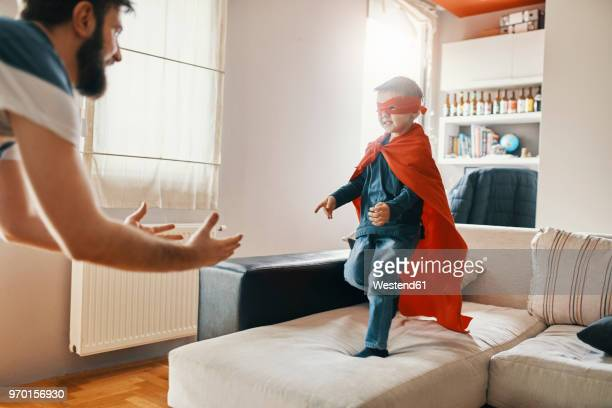 father playing with his little son dressed up as a superhero at home - cape garment stock photos and pictures