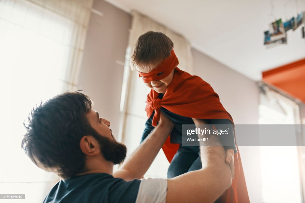 Father playing with his little son dressed up as a superhero : Stock Photo