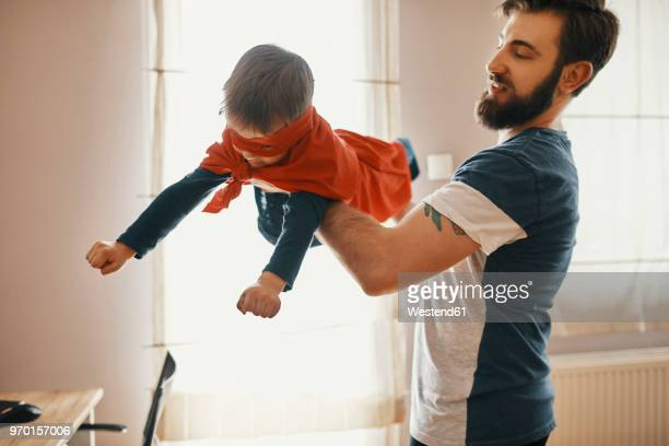 father playing with his little son dressed up as a superhero - hero stock photos and pictures