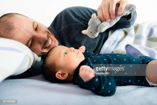 Father playing with his newborn baby girl and a a cuddly toy on bed