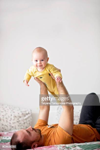 Father, playing with his son at home, holding him like airplane in the air, baby smiling happily