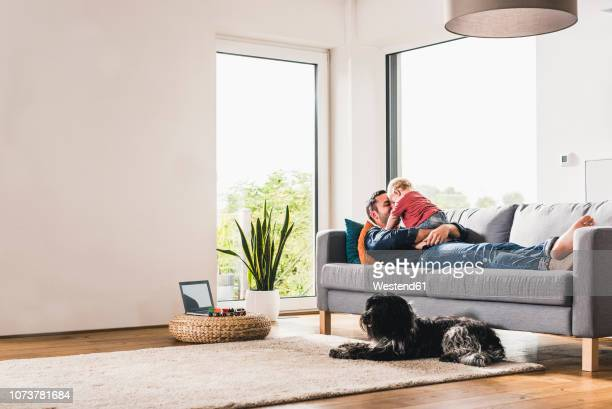 father playing with his son at home - comfortable stock pictures, royalty-free photos & images