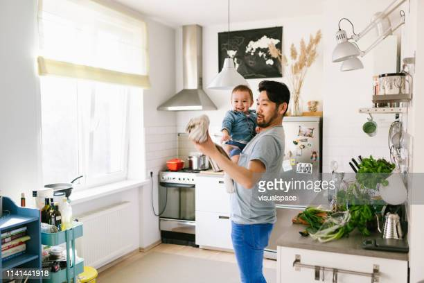father playing with his son in the kitchen - brightly lit stock photos and pictures