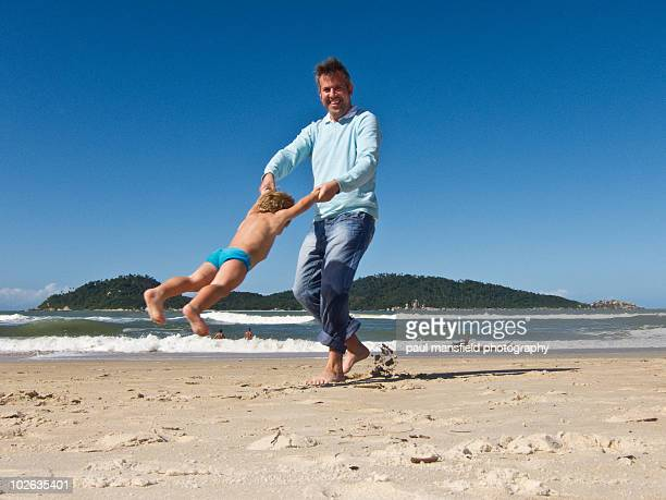 Father playing with his son on sandy beach