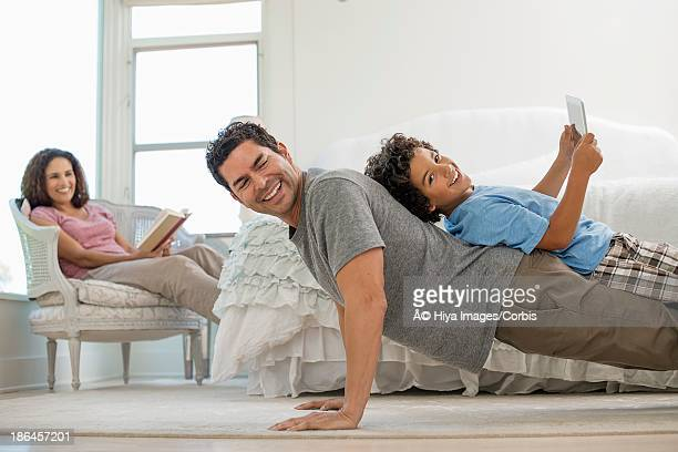 Father playing with his son while mother is watching them