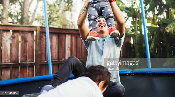 Father playing with kids on trampoline.