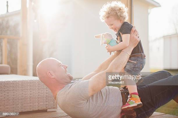 Father playing with little daughter on terrace
