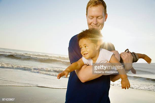 Father playing with mixed race son at beach