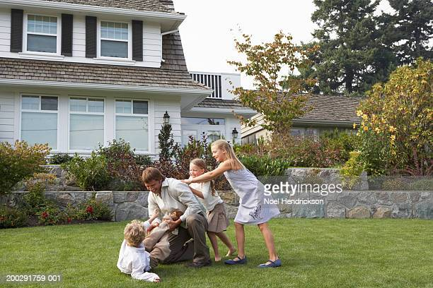 Father playing with son (5-7 years) and two daughters (6-12 years) in garden