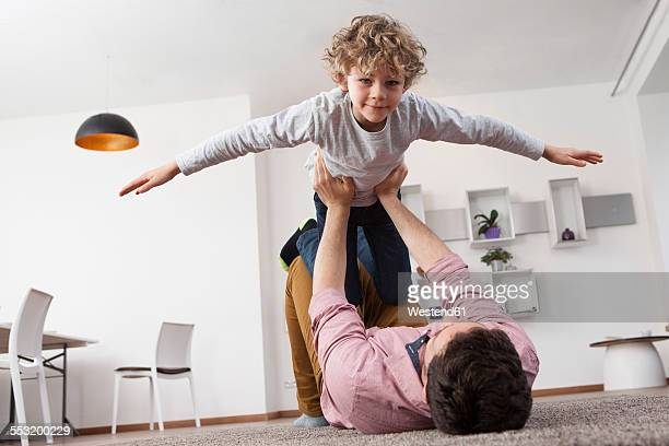 Father playing with son at home