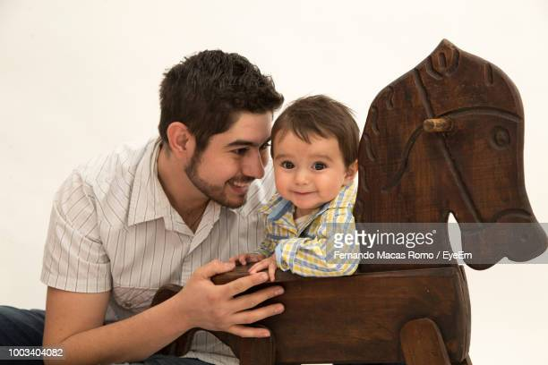 Father Playing With Son By Rocking Horse Against White Background
