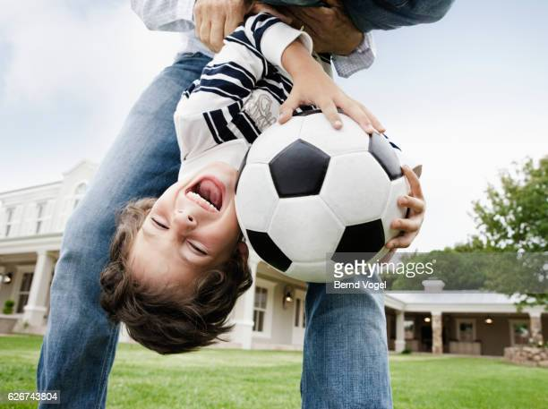 Father playing with son in backyard