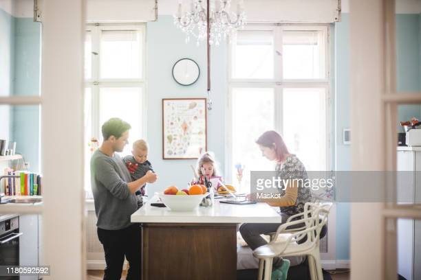 father playing with son while standing by girl and woman busy at kitchen island - familie stock-fotos und bilder