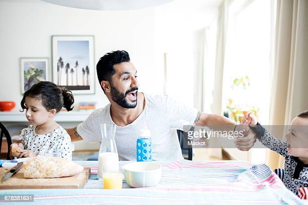 Father playing with toddler while sitting by daughter during breakfast at home