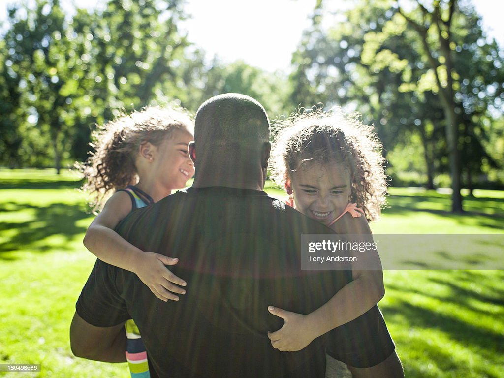 Father playing with twin daughters in park : Stock Photo
