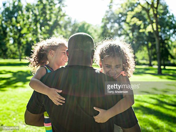 father playing with twin daughters in park - leanintogether stock pictures, royalty-free photos & images