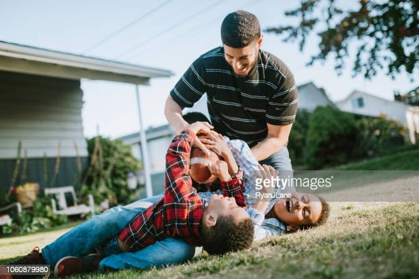 father plays football outside with his sons - tackling imagens e fotografias de stock