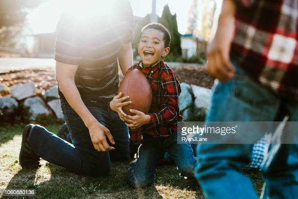 Father Plays Football Outside With His Sons