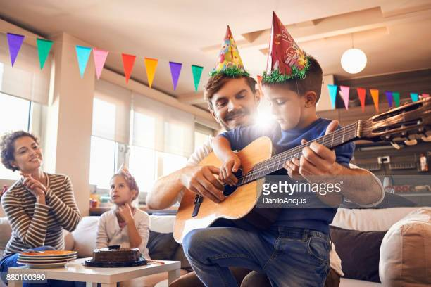 father plays guitar with his son and celebrating birthday