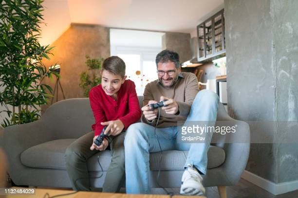 father plays video games with his little boy - family with one child stock pictures, royalty-free photos & images