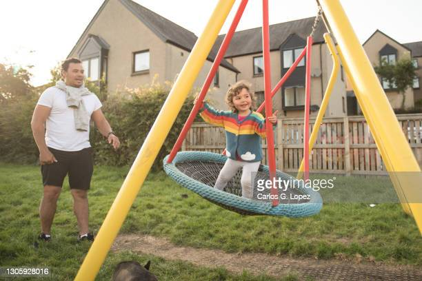 a father plays with her daughter on a swing in a public play park - real people stock pictures, royalty-free photos & images