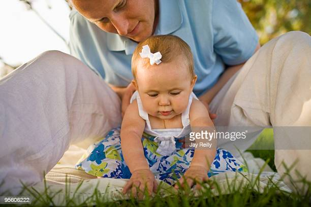 a father plays with his baby girl, while sitting on a picnic blanket outside on a sunny day in calif - hair bow stock pictures, royalty-free photos & images